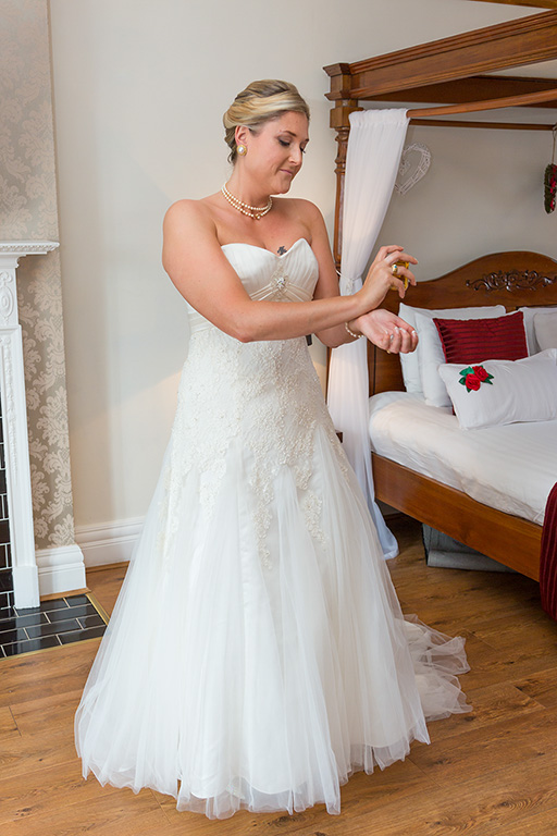 bride putting on perfume in the bridal suite