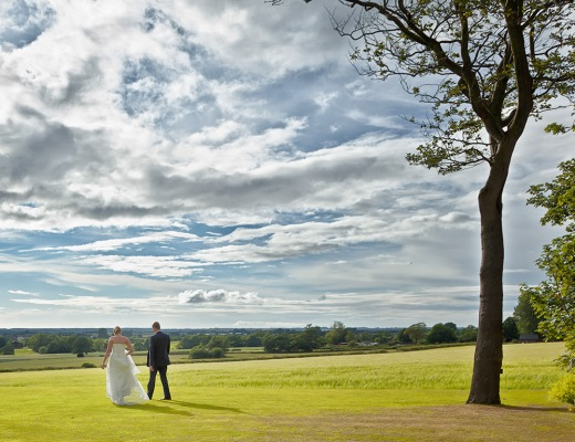 Bride & Groom on a Long Walk The West Tower Hotel with view over the Irish sea.